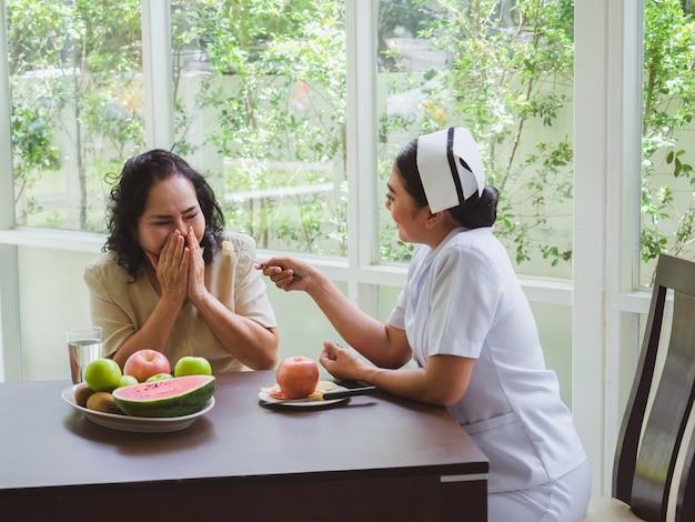 看護師はリンゴを高齢者に与えています、年配の女性は果物を食べたくありません