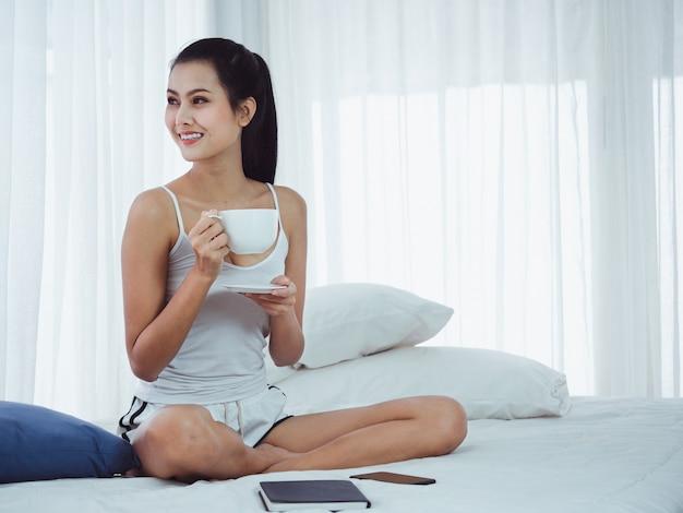 女性はベッドでコーヒーを飲んでいます