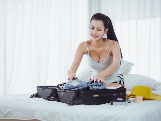 アジアの美しい女性が休日に行くバッグを準備しています