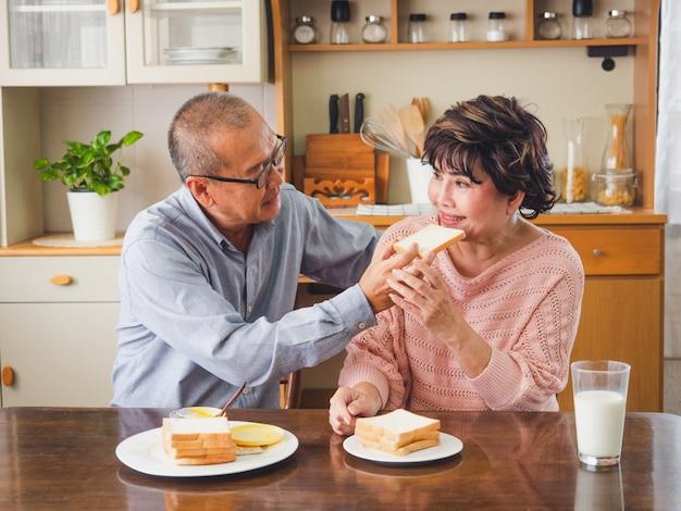 年配のカップルは朝食を一緒に食べています、男性は女性が食べるためにパンを入れます