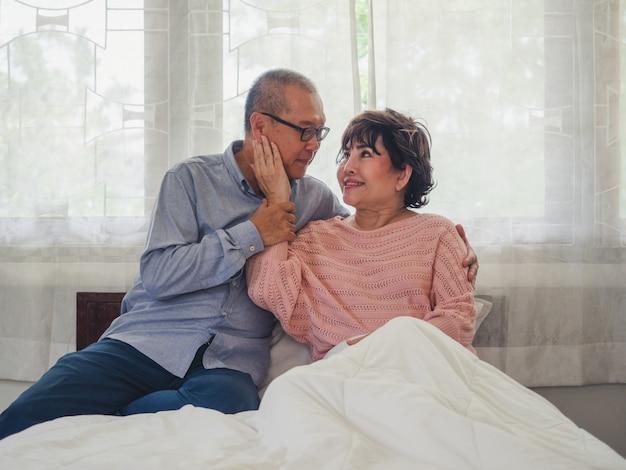 年配のカップルが座ってベッドで休む