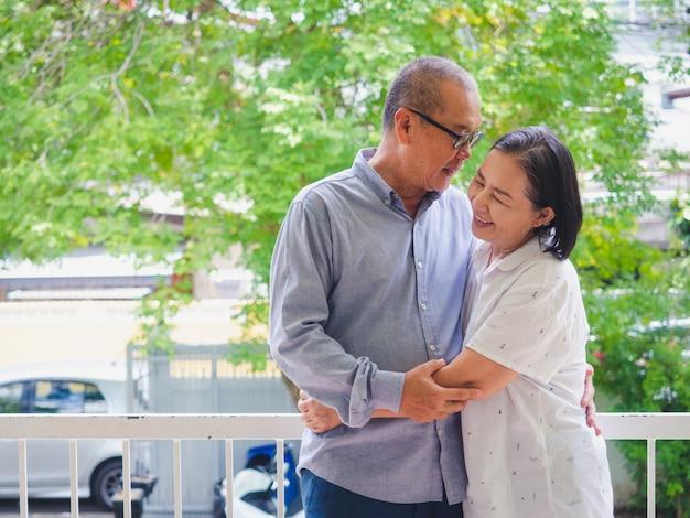 バルコニーで抱きしめる老夫婦