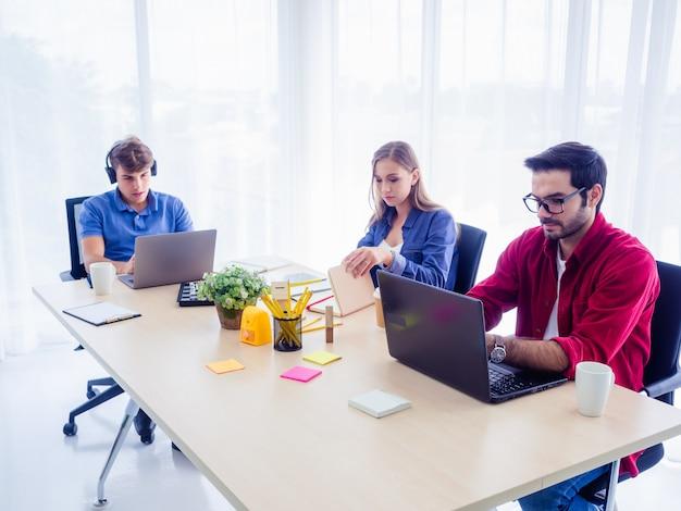 Деловые люди работают и сидят за офисным столом вместе