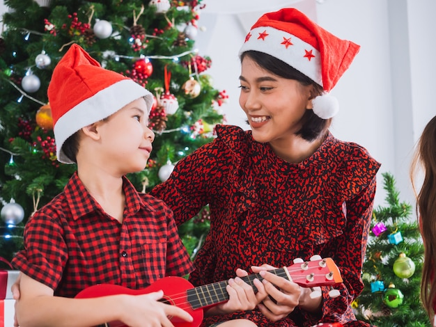 母は家でクリスマスを祝う少年、家族とクリスマスの日にギターを弾いていた