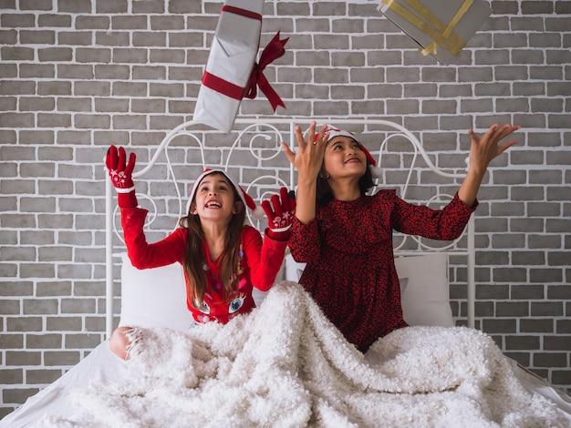 Мать и дочь празднуют рождество, бросая подарочную коробку в воздух