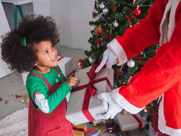Малыш с удовольствием получает подарки от деда мороза