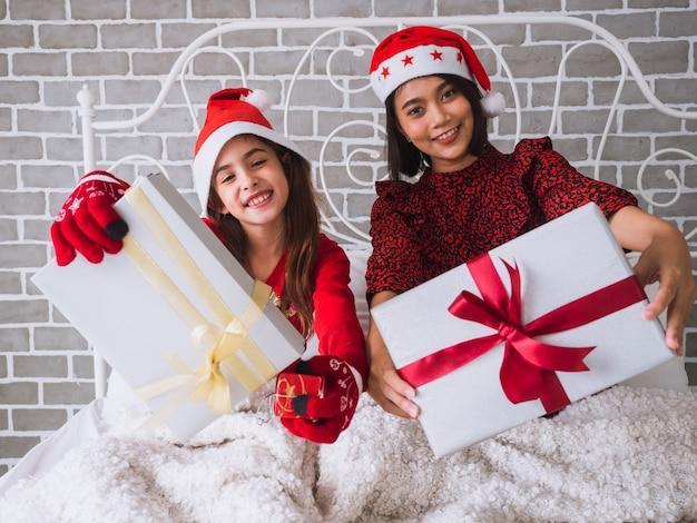 Мать и дочь показывают подарочную коробку и празднуют рождество на кровати