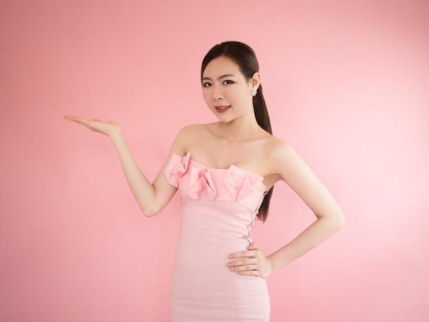 セクシーな女性が手に何かを見せ、アジアの女の子がストラップレスドレスを着てポーズをとる