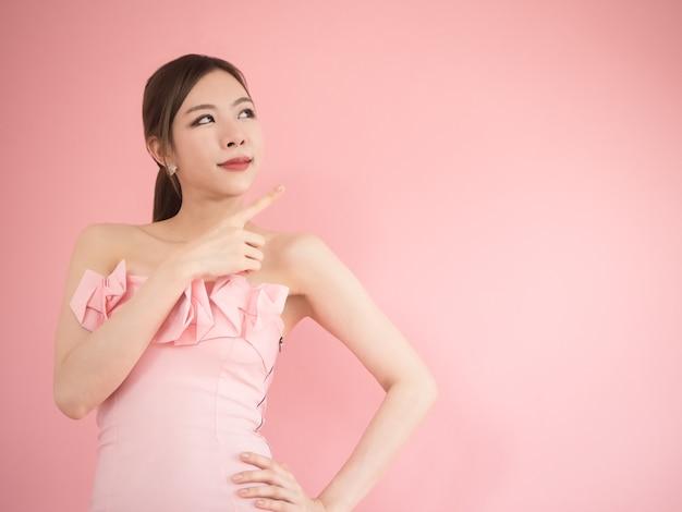 アジアの女の子を見上げて、ピンクの背景にポーズを当てる美しい女性。
