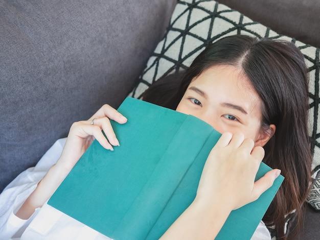 アジアの女性が座って、家のソファーで本を読んで
