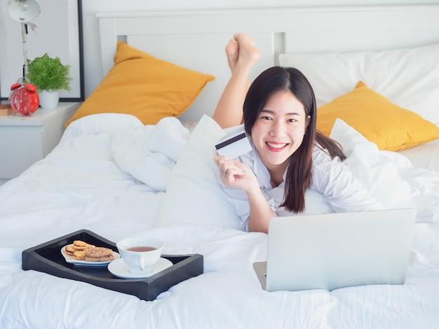 アジア人、女の子、ベッド、クレジットカード、コンピュータ
