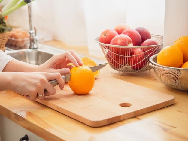 キッチンに果物を入れたアジア人女性
