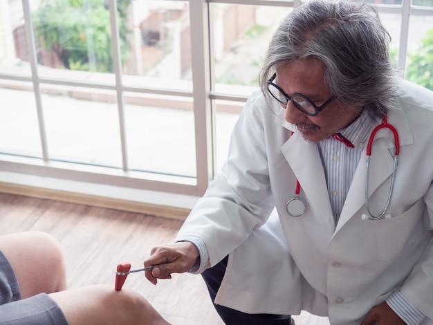 医者は患者の膝を検査している