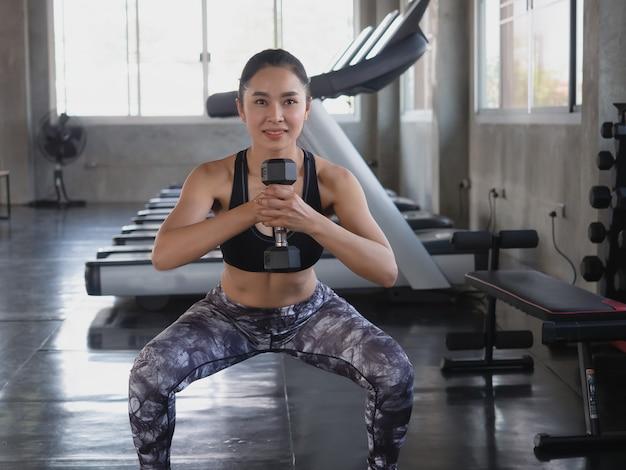 アジアの女性はジムでダンベル運動します。