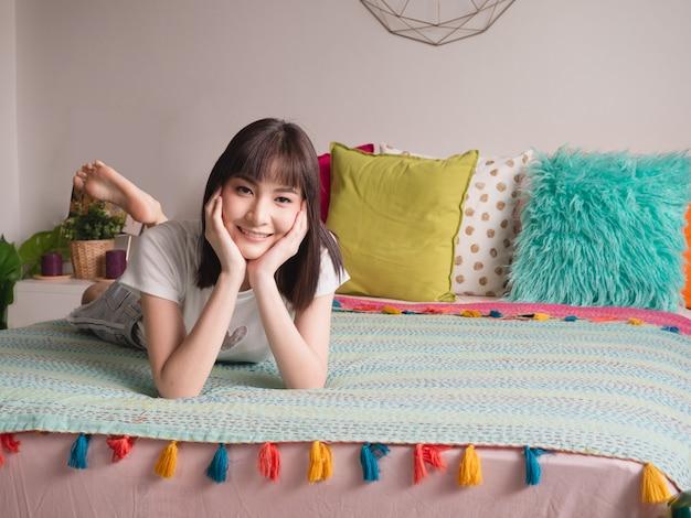 ベッドであごに横になっている女性