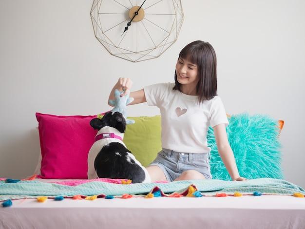 犬がベッドの上で遊んでいる女性