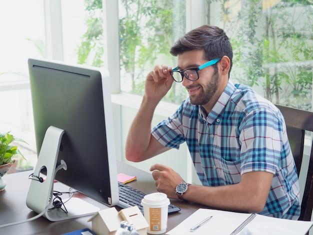 若い男が眼鏡と笑顔で在宅勤務