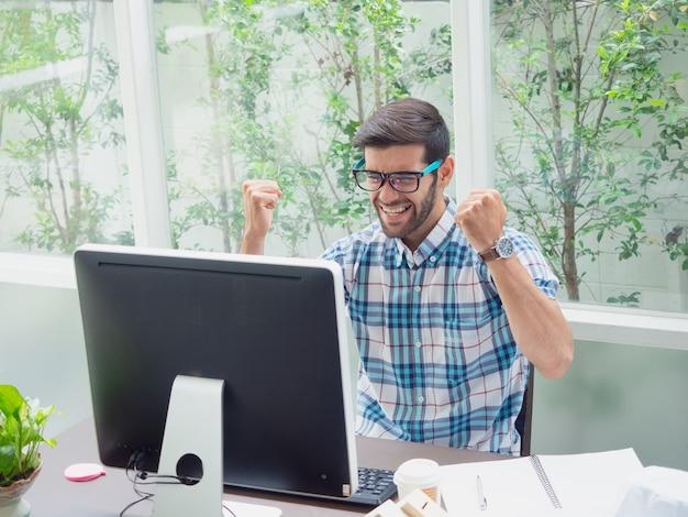 若い男が自宅で仕事と仕事について幸せ