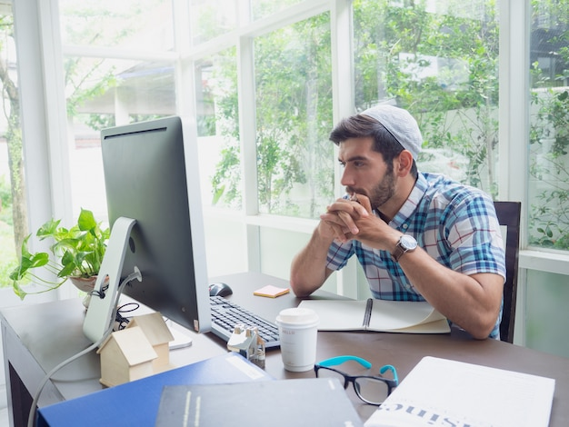 若い男が自宅で仕事と何かを考えて