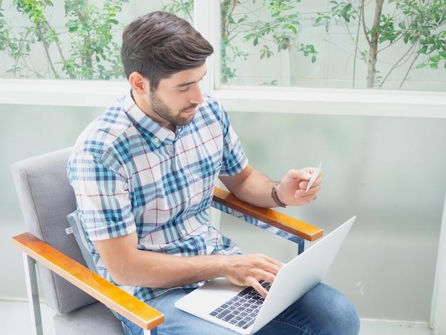 若い男が自宅でクレジットカードでオンラインショッピング