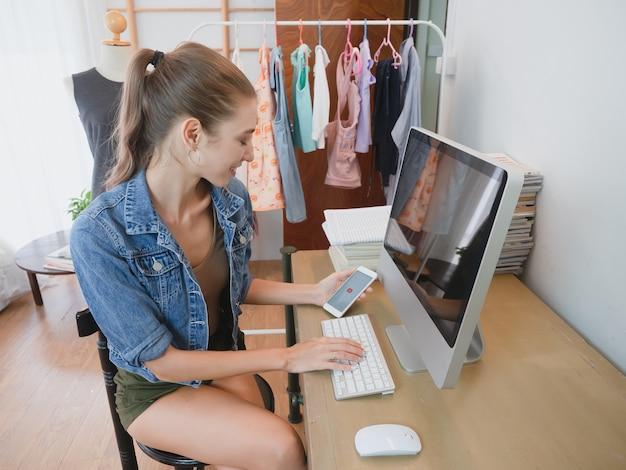 女性はオンライン販売についてのコンピューターを介して顧客の質問に答えている、彼女の家でビジネスをしている女の子