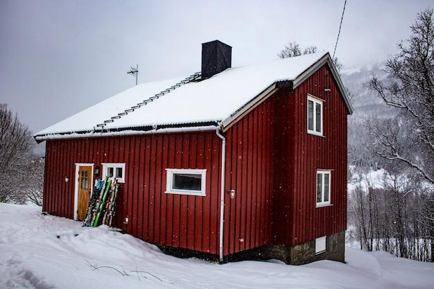 冬の間、ノルウェーの家の前にスキーと赤いノルウェーのコテージ