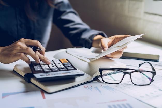 Подчеркнул молодая женщина, проверка счетов, налогов, баланса банковского счета и расчета расходов в гостиной дома