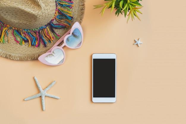 色の背景とコピースペース、夏の休暇の概念にスマートフォンでアクセサリーアイテムを旅行します。