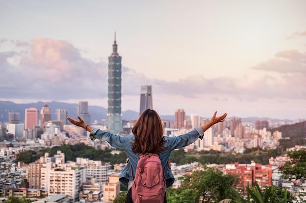 Путешественник молодой женщины смотря красивый городской пейзаж на заходе солнца в тайбэе
