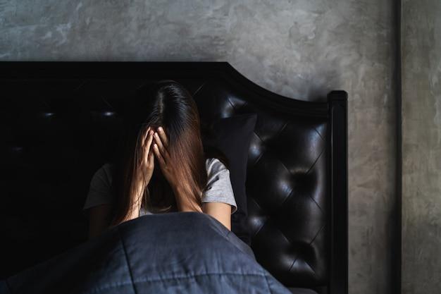 Одинокая молодая женщина в депрессии и стресс, сидя в темной спальне