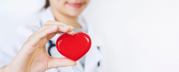 Молодая женщина-врач со стетоскопом держит красное сердце
