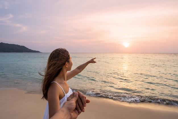 Путешественник молодой женщины держа руку человека и смотря красивый заход солнца на пляже, пары на каникулах в концепции лета