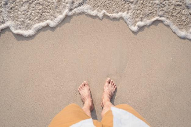 若い旅行者と夏の熱帯の砂浜にソフトオーシャンウェーブ