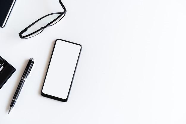 空の画面のスマートフォンとコピースペース、トップビューでビジネスデスクオフィスのファイルフォルダー