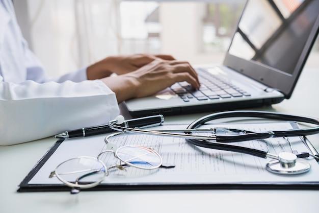医師が病院でラップトップを使用して、ヘルスケアおよび医学の概念