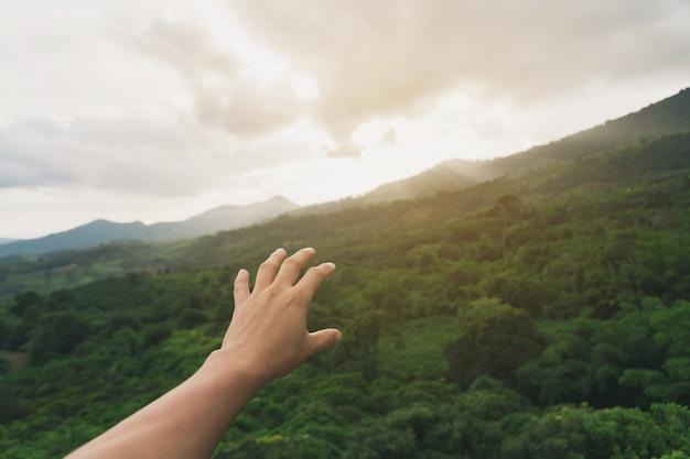 日没時に山に手を伸ばす若い男の手