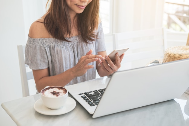 カフェでコーヒーのカップを持つスマートフォンとラップトップを使用して若い女性