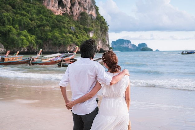 タイ、クラビの熱帯の砂浜で夏休みを楽しんでいる若いカップル旅行者