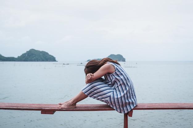 海に一人で座って落ち込んでいると強調した若い女性