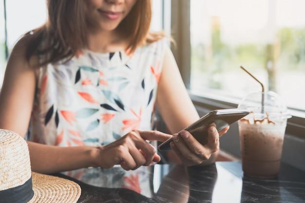 カフェでドリンクを飲みながらスマートフォンを使用して若い女性