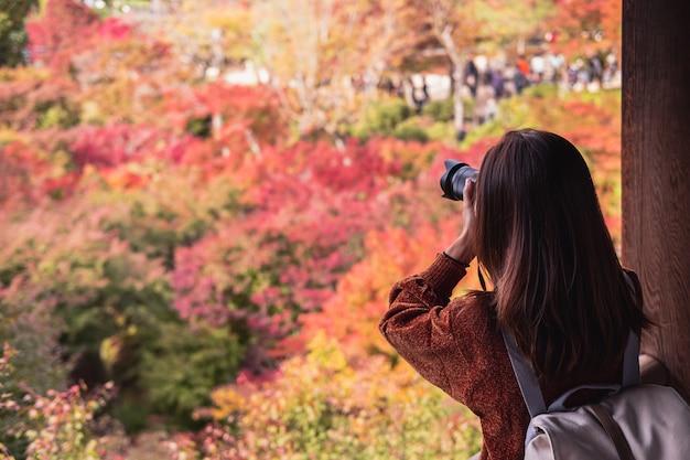 若い女性旅行者を探して、日本、旅行ライフスタイルコンセプトの美しい秋を撮影