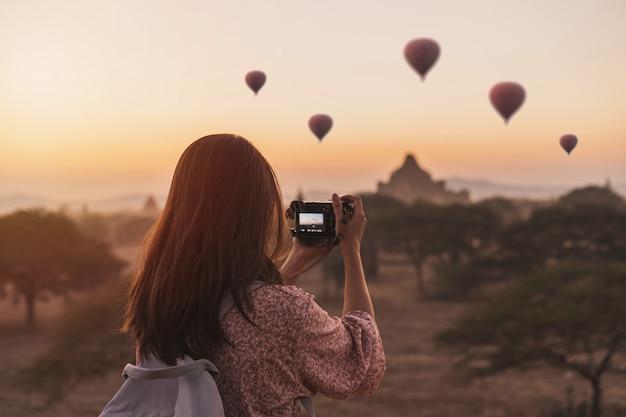 日の出ミャンマーバガンで古代の塔の上に風船で楽しむ若い女性旅行者