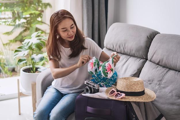 若いアジアの女性が彼女のスーツケースを梱包