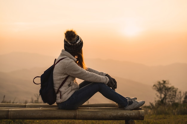 Молодая женщина-путешественник, глядя на восход солнца