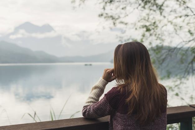寂しい女性が不在のままに立って、川を見て