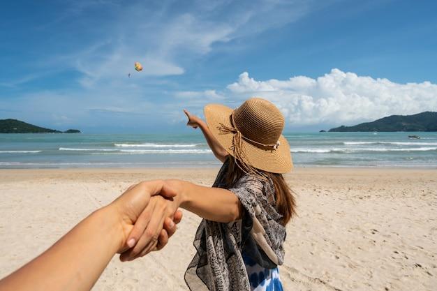 Молодая женщина-путешественник держит руку человека и смотрит парашют в небе на пляже