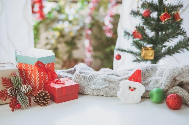 居心地の良い家の白い木製のテーブルのクリスマスの贈り物、装飾品および装飾のコレクション