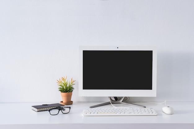 コピースペースを持つデスクオフィスに空のスクリーンコンピューターモニター