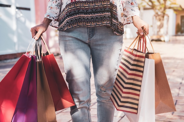ブラックフライデーのショッピングモールで買い物袋を持つ若い女