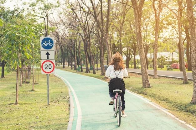 公園の自転車レーンで若い女性乗馬自転車